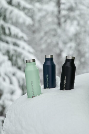 Three insulated, recyclable Muntagnard bottles stuck in the snow in front of a snow-covered Christmas tree.