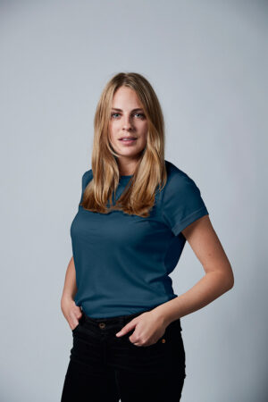 Woman is wearing blue wooden T-shirt from the LEGNA line by Muntagnard. Image taken from the front, with a gray background.