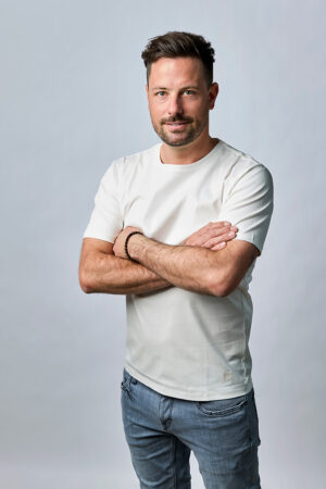 Guy posing with MANGOLA Men Crew Neck T-Shirt and a jeans. His arms are crossed, background is grey.